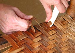 Using a bone folder to help with the weaving.